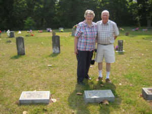 Bill and Jane Maxwell at the graves of Edmond Dutton and Margaret Barnett Ross.